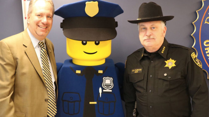 "District Attorney David Hoovler (left) and Sheriff Carl E. DuBois (right) with LEGOLAND New York's ""Police Officer Parks"" outside of Hoovler's office at the Government Center."