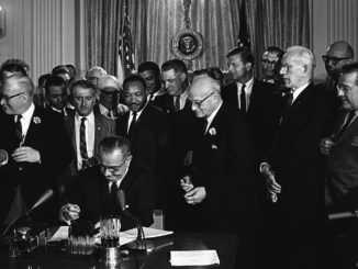 President Lyndon B. Johnson signs the 1964 Civil Rights Act as Martin Luther King, Jr., and others, look on, July 2, 1964. Photo: Cecil Stoughton, White House Press Office (WHPO), via Wikimedia Commons