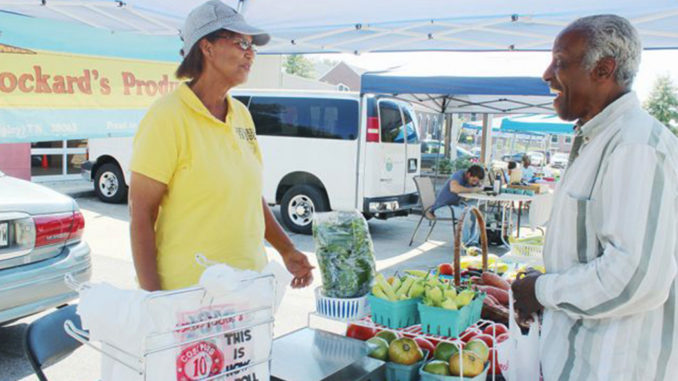 """""""(Being a farmer) pays off when a customer comes back and tells me how good (my produce) tastes,"""" said Debra Lockard, shown here talking shop with a patron at the South Memphis Farmers Market in October. (Photo: Lee Eric Smith)"""