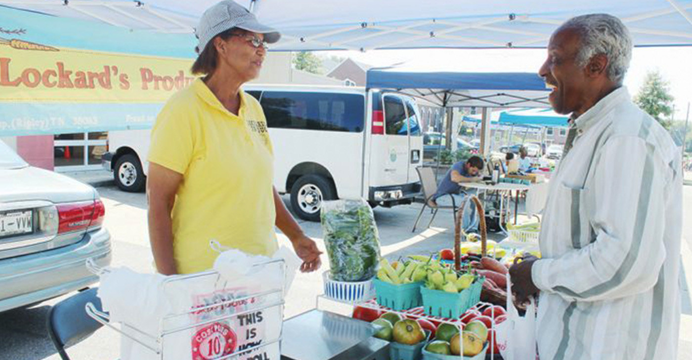"""(Being a farmer) pays off when a customer comes back and tells me how good (my produce) tastes,"" said Debra Lockard, shown here talking shop with a patron at the South Memphis Farmers Market in October. (Photo: Lee Eric Smith)"