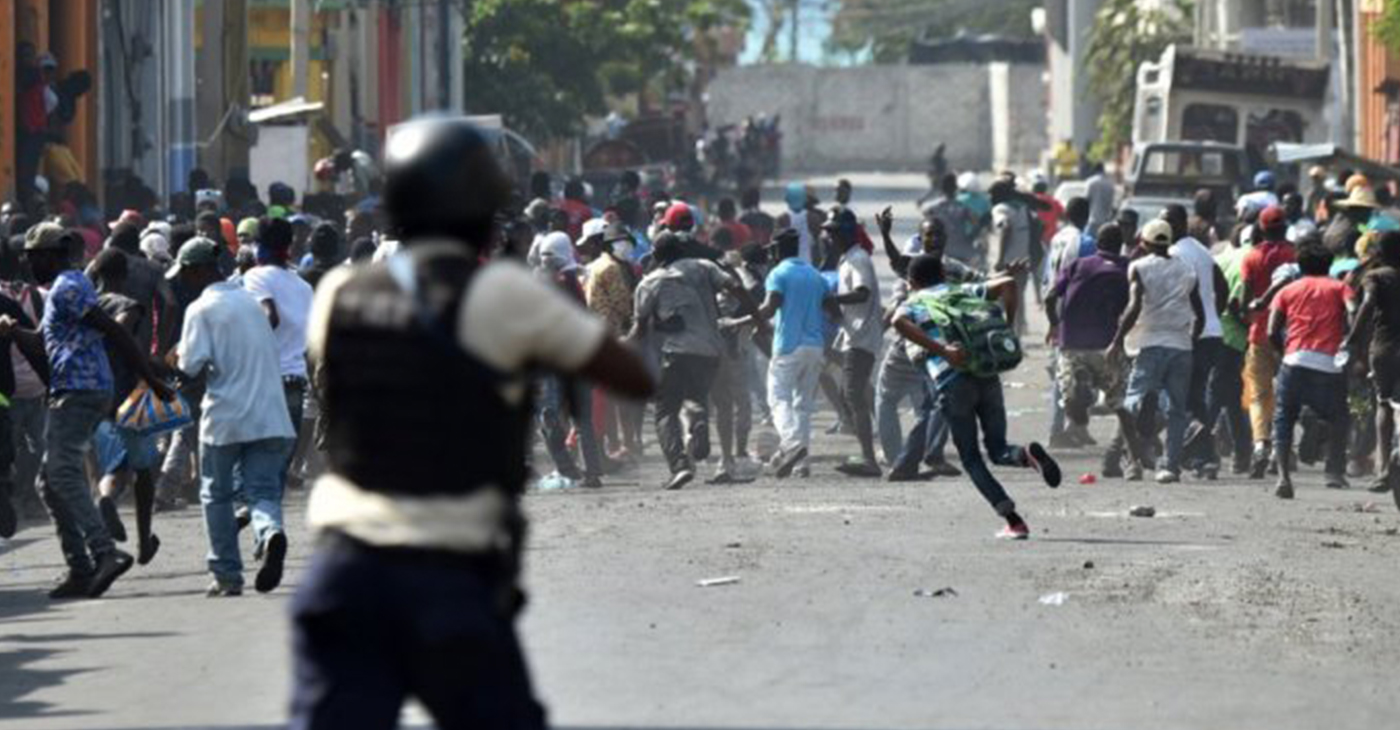 Demonstrators flee as Haitian police open fire during the clashes in the center of the Haitian capital Port-au-Prince on Feb. 13, 2019, the seventh day of protests against Haitian President Jovenel Moise that continue unabated. – Photo: Hector Retamal, AFP