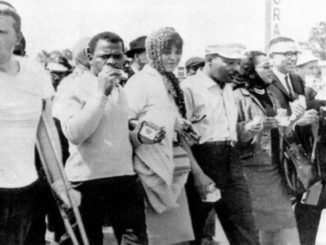 C. Delores Tucker, center, walks hand-in-hand with Rev. Martin Luther King Jr., fourth from left, during a 1965 march in Alabama (Submitted Photo)