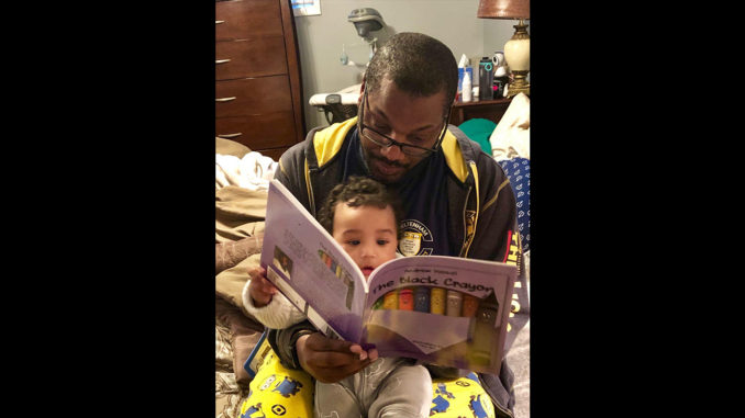 """""""The Black Crayon"""" author Andrew Vassall reads his book to his son, Shaan Ivan Vassall. The story encourages reading and teaches self-awareness and cultural awareness to young children. (Photo Courtesy of Andrew Vassal)"""