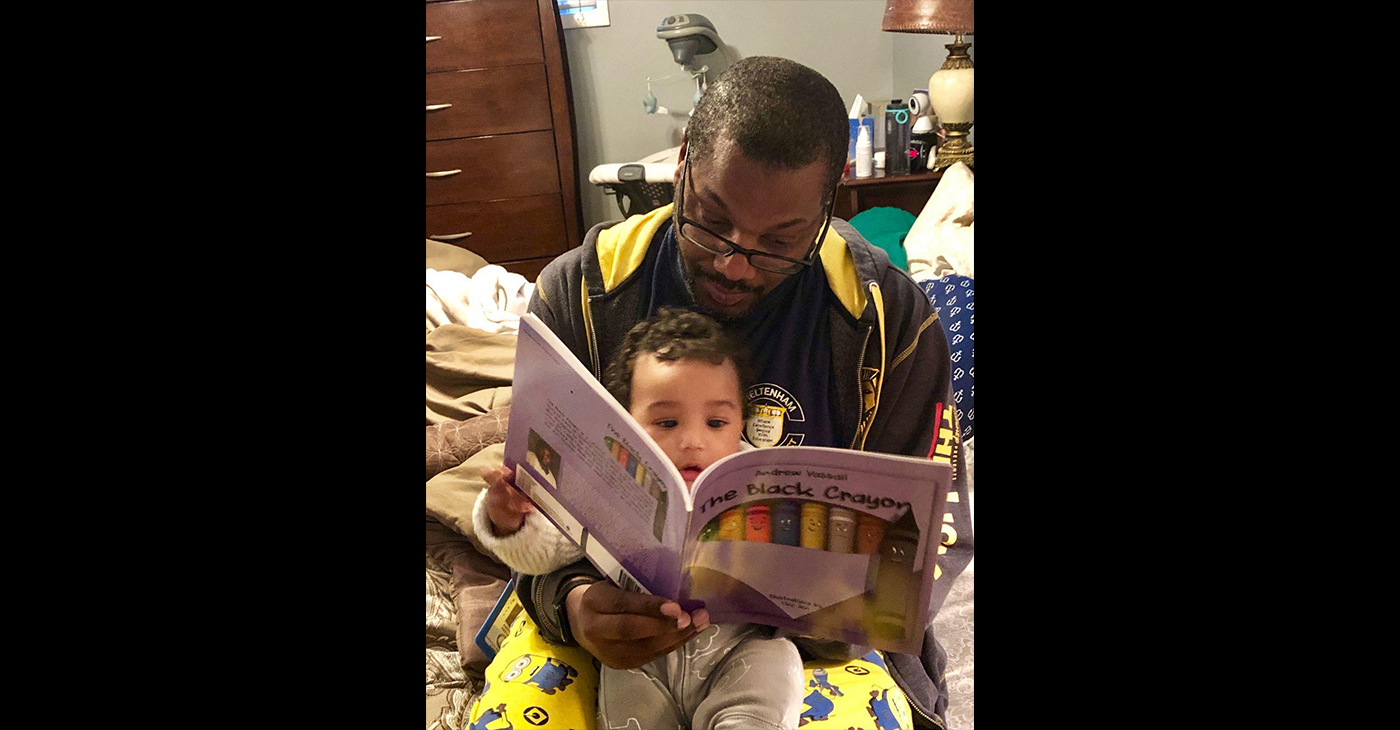 """The Black Crayon"" author Andrew Vassall reads his book to his son, Shaan Ivan Vassall. The story encourages reading and teaches self-awareness and cultural awareness to young children. (Photo Courtesy of Andrew Vassal)"