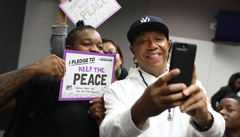 "Russell Simmons takes a selfie with a student from the Community Coalition's Freedom School, during RushCard's ""Keep The Peace"" initiative at the University of Southern California. (File Photo: Andre L. Perry/Los Angeles Sentinel)"