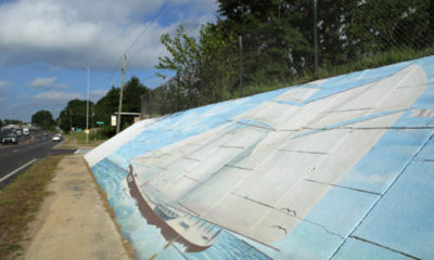 A mural of the Clotilda is painted on a retaining wall beneath the Peter Lee homeplace in Africatown on Wednesday, May 29, 2019, in Mobile, Ala. (Mike Kittrell)
