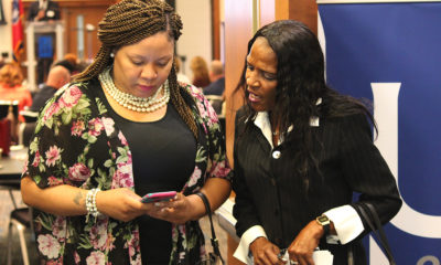 "Lori Black (right) shares her information with a new contact interested in helping the 52-year-old ex-offender find work. The two met at a forum aimed at connecting employers with the formerly incarcerated. ""My background don't determine me,"" a defiant but determined Black said. ""Not today, it don't."" (Photo: Lee Eric Smith)"