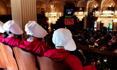 "Women dressed as Handmaids, characters from Margaret Atwood's dystopian novel, ""The Handmaid's Tale,"" watch as Rep. Kelly Cassidy, D-Chicago, presents her arguments in favor of the Reproductive Health Act on the floor of the House in Springfield (Capitol News Illinois photo by Rebecca Anzel)."