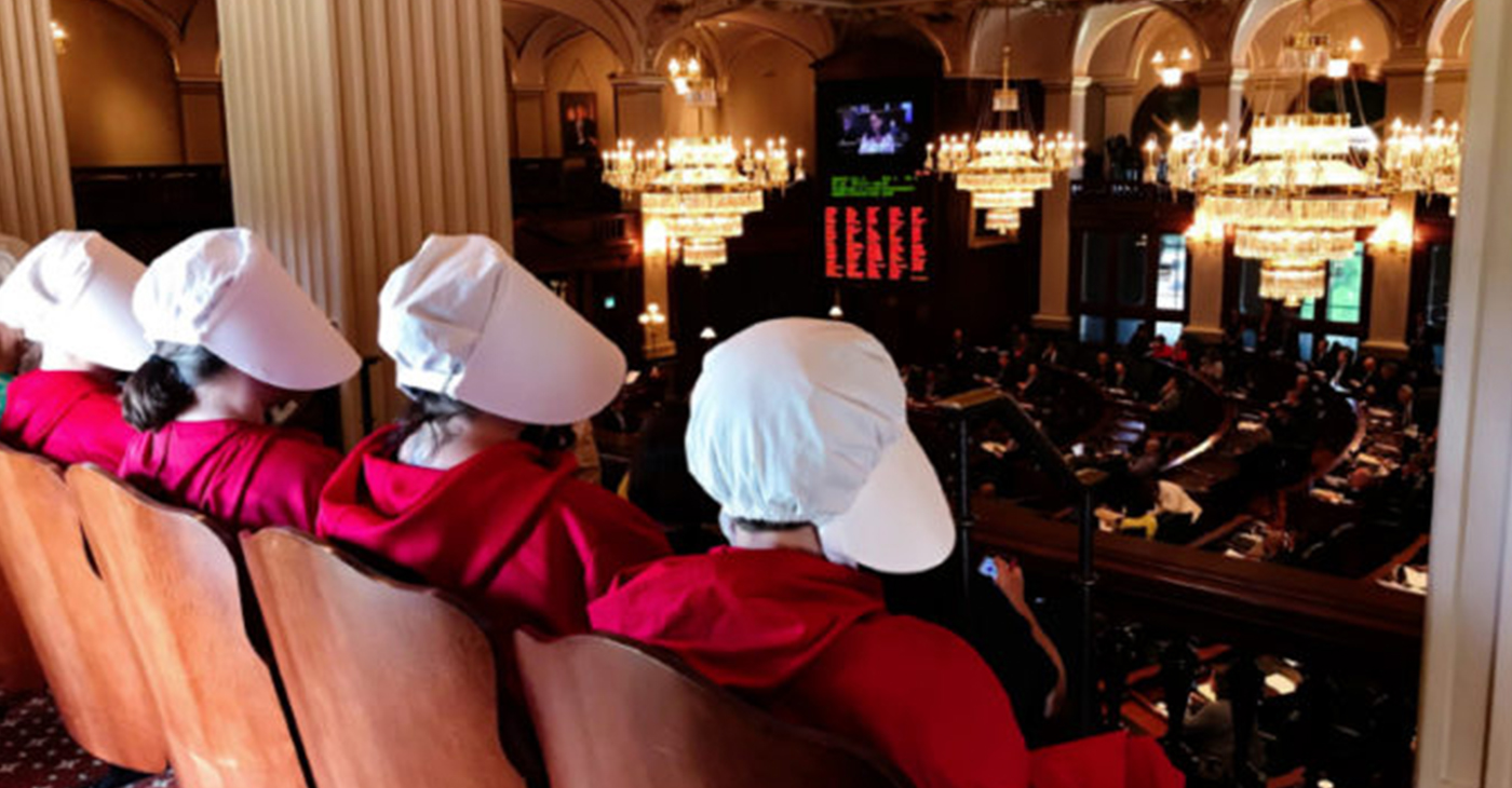"""Women dressed as Handmaids, characters from Margaret Atwood's dystopian novel, """"The Handmaid's Tale,"""" watch as Rep. Kelly Cassidy, D-Chicago, presents her arguments in favor of the Reproductive Health Act on the floor of the House in Springfield (Capitol News Illinois photo by Rebecca Anzel)."""